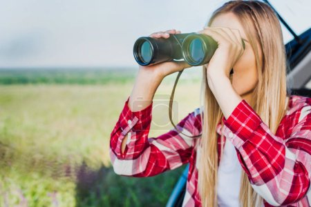young female traveler looking through binoculars near car in rural field