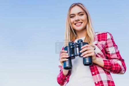 smiling female traveler holding binoculars against blue sky