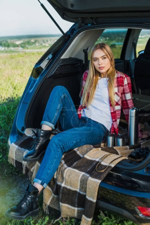 Photo for Young woman sitting on car trunk with coffee cups and thermos in rural field - Royalty Free Image