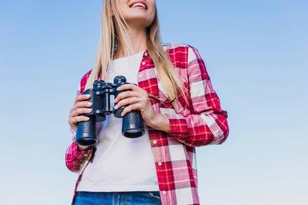 Foto de Recortar el tiro de viajero mujer con prismáticos contra el cielo azul - Imagen libre de derechos