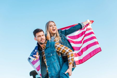 stylish man doing piggyback ride to girlfriend holding american flag against blue sky, independence day concept