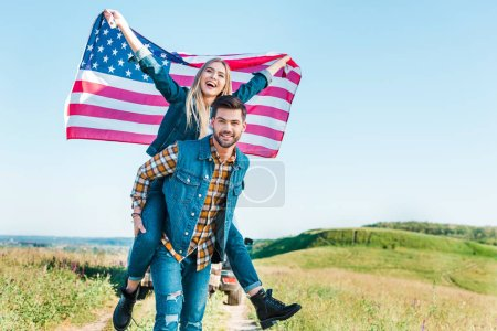young man doing piggyback ride to girlfriend holding american flag on rural meadow, independence day concept