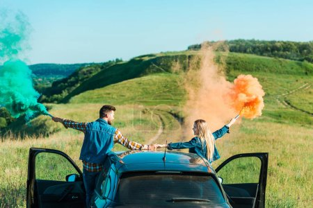 rear view of couple with colorful bombs standing on car and holding hands on rural meadow