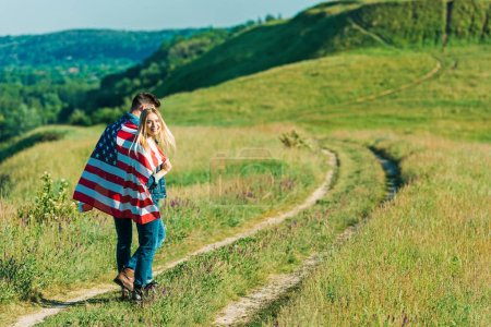 back view of young couple with american flag on rural meadow, independence day concept