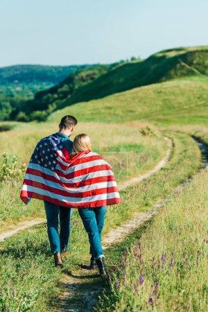 vue arrière du jeune couple avec drapeau américain sur pré rural, concept de la fête de l'indépendance
