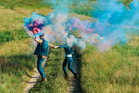 back view of couple holding colorful smoke bombs in rural field