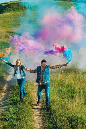 elevated view of smiling couple holding colorful smoke bombs on rural meadow
