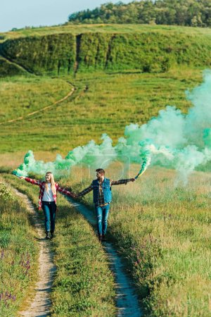 elevated view of young couple holding green smoke bombs on rural meadow