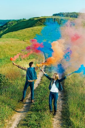 view from above of young couple holding colorful smoke bombs on rural meadow