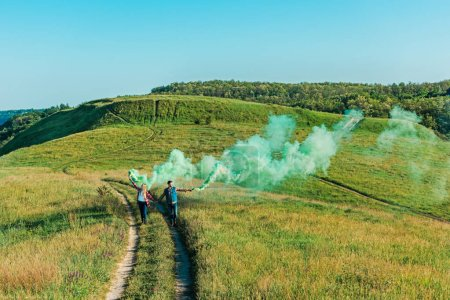 distant view of young couple holding green smoke bombs on rural meadow