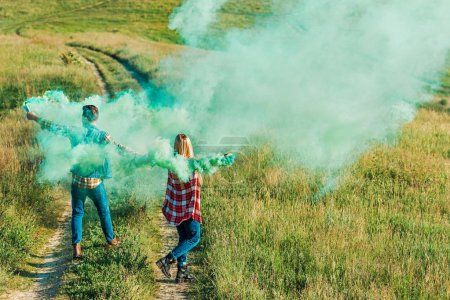back view of young couple holding green smoke bombs on rural meadow