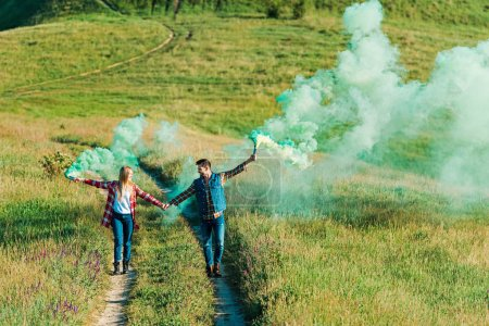 young couple holding green smoke bombs on rural meadow