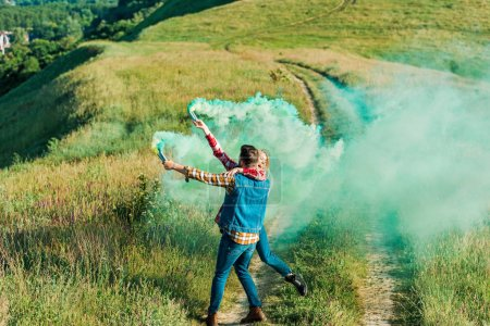 back view of man holding girlfriend and green smoke bombs on rural meadow
