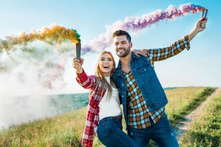 smiling couple holding colorful smoke bombs on rural meadow