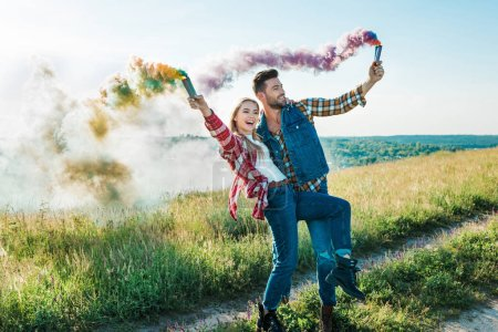 happy young couple holding colorful smoke bombs on rural meadow