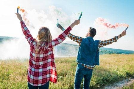 rear view of young couple holding colorful smoke bombs on rural meadow