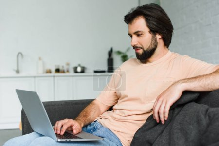 side view of smiling man using laptop while resting on sofa at home