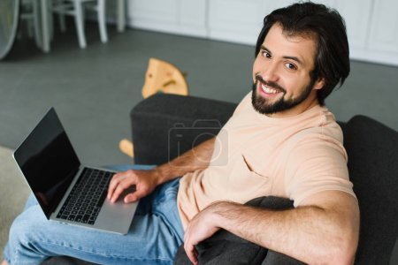 side view of smiling man with laptop resting on sofa at home