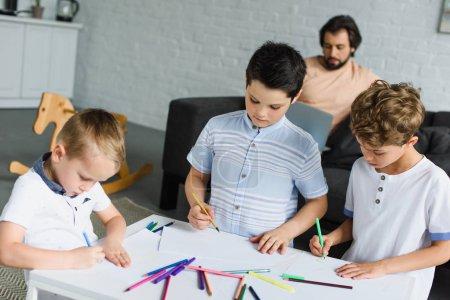 Foto de Niños hacer dibujos con lápices de colores mientras padre utilizando la computadora portátil en el sofá en casa - Imagen libre de derechos