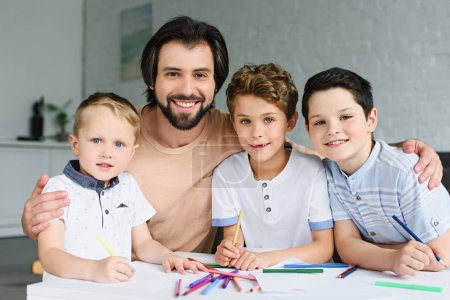 portrait of smiling father and sons at table with papers and colorful pencils at home
