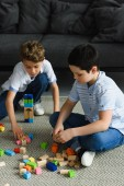 little boys playing with wooden blocks on floor at home