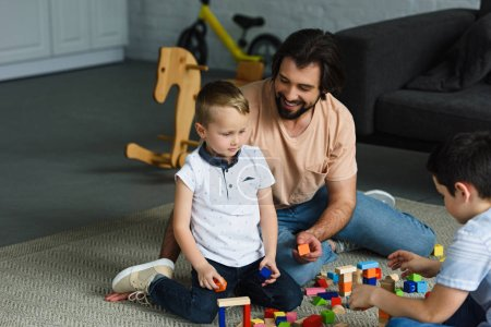 father and kids playing with wooden blocks together on floor at home