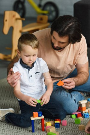 father hugging little son while playing with wooden blocks together at home