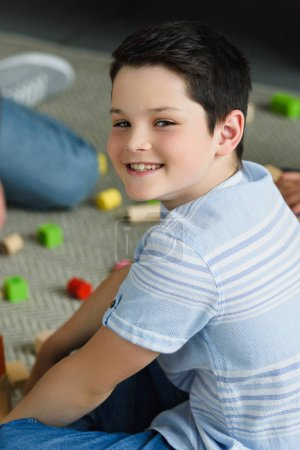 side view of smiling boy looking at camera while sitting on floor with wooden blocks at home