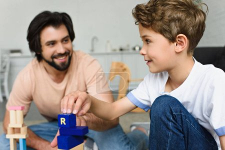 selective focus of father and son playing with wooden blocks together at home
