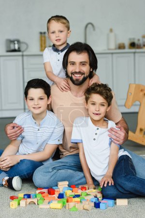 happy father hugging little sons and looking at camera while sitting on floor with wooden blocks at home