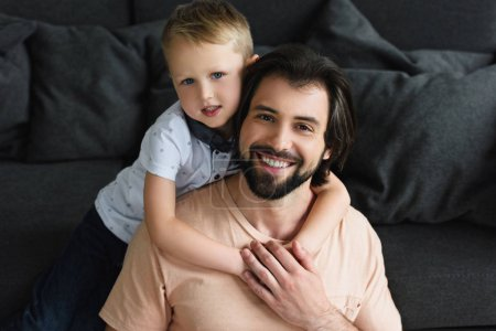 high angle view of little son hugging happy father on sofa at home