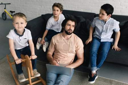tired father with laptop and little kids sitting on sofa around at home