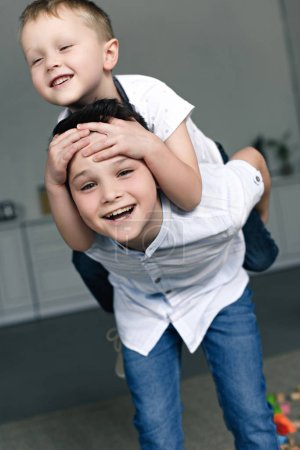 Photo for Portrait of happy brothers piggybacking together at home - Royalty Free Image