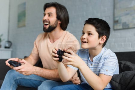Photo for Side view of smiling father and son playing video games together at home - Royalty Free Image