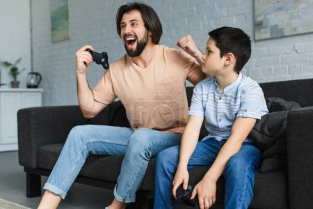 emotional father and son playing video games together at home