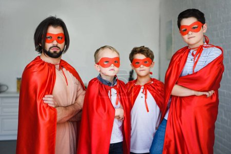 portrait of father and little sons in red superhero costumes with arms crossed at home