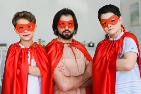 portrait of father and sons in red superhero costumes with arms crossed looking at camera at home