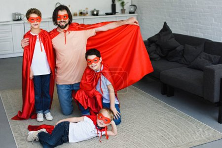 smiling father and sons in red superhero costumes at home