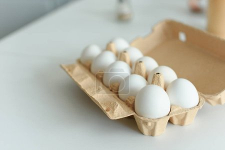 close up view of raw chicken eggs in box on tabletop in kitchen