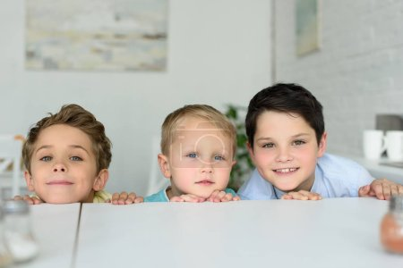 little boys hiding behind table and looking at camera at home