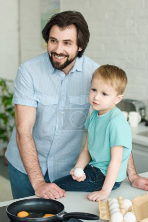 portrait of smiling father and little son with raw egg in hand in kitchen at home