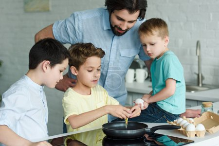 Photo for Portrait of family cooking eggs for breakfast together in kitchen at home - Royalty Free Image