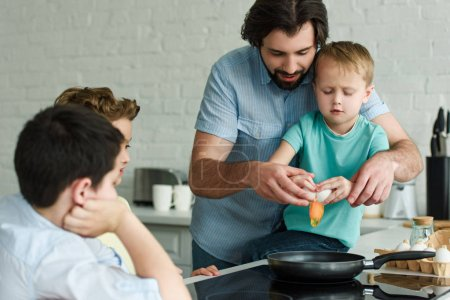 family cooking eggs for breakfast together in kitchen at home