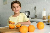 portrait of little boy standing at counter with fresh oranges in kitchen at home