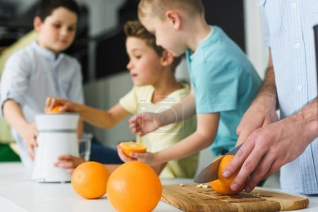 partial view of family making fresh orange juice in kitchen at home
