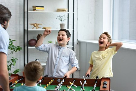 father and happy little sons playing table football together at home