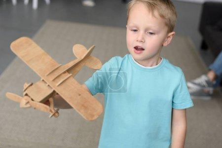 Foto de Retrato de niño lindo con plano de madera del juguete en mano en casa - Imagen libre de derechos