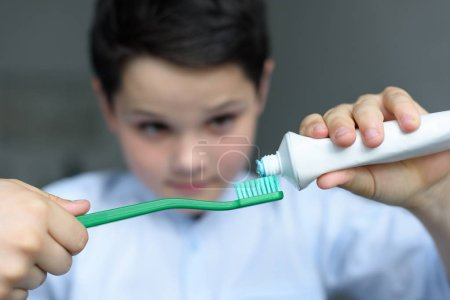 selective focus of little boy putting tooth paste on tooth brush in hand at home
