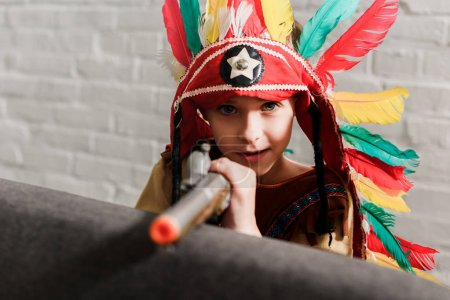 little boy in indigenous costume with toy gun playing at home