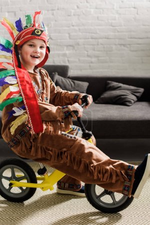 happy little boy in indigenous costume on runbike playing at home